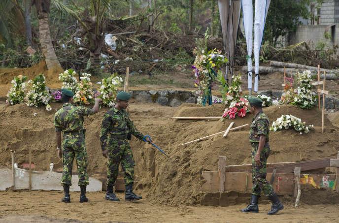 Trois jours après l'attentat du 21 avril, les forces de l'ordre sri-lankaises sécurisent le site d'un enterrement collectif de victimes, à Negombo.