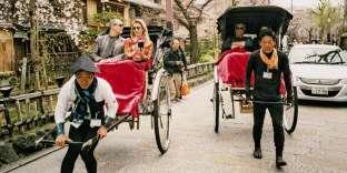 Le long du canal Shirakawa, dans le quartier de Gion, à Kyoto. Piétons, pousse-pousse (jinrikisha en japonais) et voitures se partagent la route.