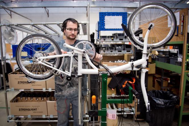 Un ouvrier de l'usineBrompton de Greenford, dans l'ouest londonien, assemble la chaîne et le pédalier d'un vélo, en janvier 2013.