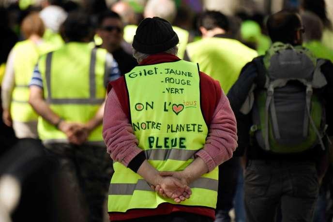 Un manifestant porte un gilet jaune sur lequel est écrit :«Gilet jaune, rouge ou vert, nous aimons tous notre planète bleue», lors d'une manifestation,le 27avril2019, àMarseille.