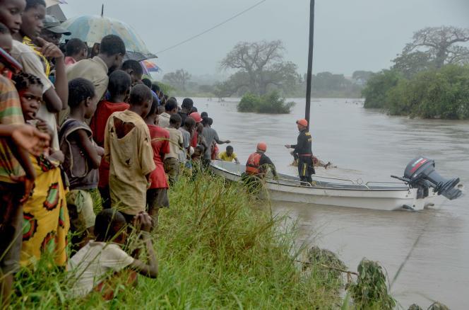 Des habitants observent une équipe de pompiers brésiliens au travail à Mazive, dans le sud du Mozambique, le 28 avril.
