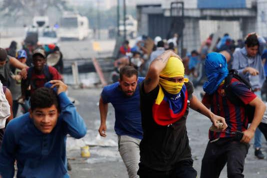 Des manifestants courent lors d'affrontements avec les forces de sécurité gouvernementales à Caracas, au Venezuela, le 30 avril 2019.