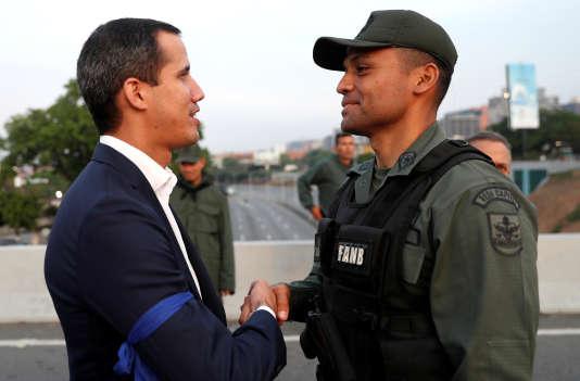 Le leader de l'opposition à Maduro, Juan Guaido, serre la main à un militaire près de la base aérienne La Carlota, à Caracas, le30avril2019.