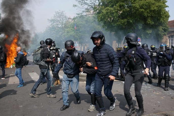 Un policier blessé est évacué par ses collègues boulevard de l'Hôpital, lors de la manifestation du 1er-Mai à Paris.