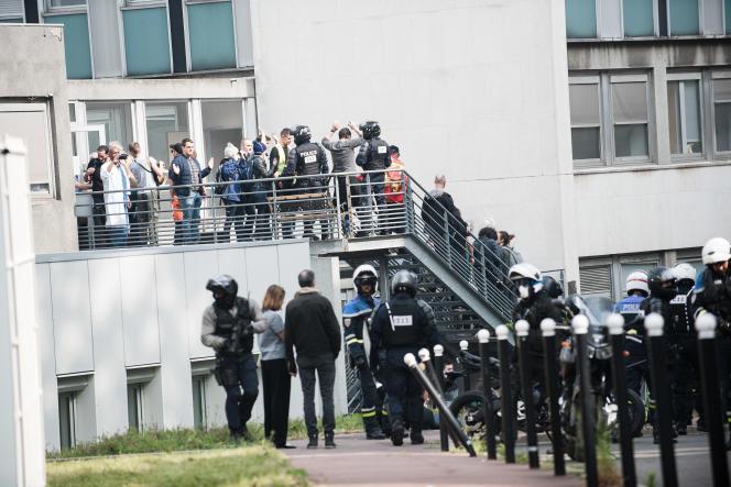 Des personnes, guidés par de nombreux policiers a moto, quittent les mains en l'air l'hopital de la Pitie Salpetriere, le 1er-mai 2019.