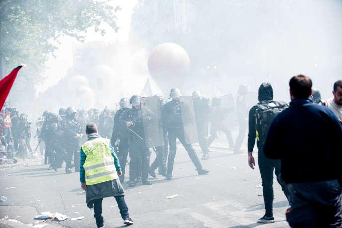 A la manifestation du 1er-Mai, à Paris,« gilets jaunes», syndicats et CRS, aumilieu d'un nuage de gaz lacrymogènes.
