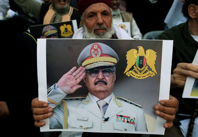 Un homme brandit une photographie de Khalifa Haftar, lors d'une manifestation àBenghazi (Libye), le 12 avril.