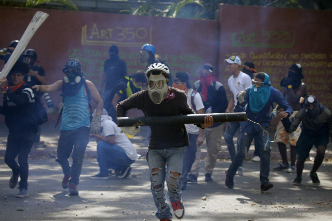 Des manifestants anti-gouvernementaux fuient les forces de sécurité qui tirent des gaz lacrymogènes pour les disperser, à Caracas, le 1er mai.