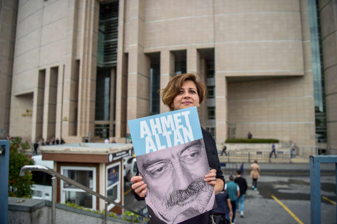 Une journaliste pose avec le portrait d'Ahmet Altan devant la Cour de justice d'Istanbul (Turquie), le 19 juin 2017.