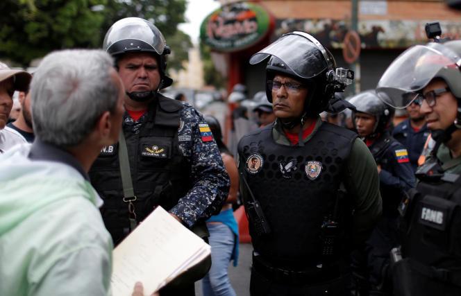 Un citoyen tente de distribuer un tract anti-Maduro à des membres de la Garde nationale, le 4 mai à Caracas.