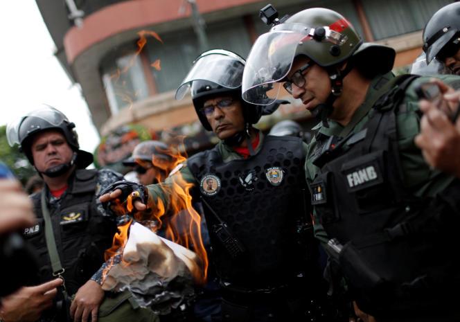 Un membre de la Garde nationale brûle le tract qu'il a reçu d'un opposant à Nicolas Maduro, le 4 mai à Caracas.