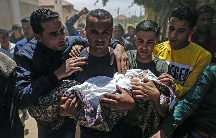 Des détenus palestiniens portent le corps enveloppé de Saba Abu Arar lors de ses funérailles à Gaza le 5 mai 2019.
