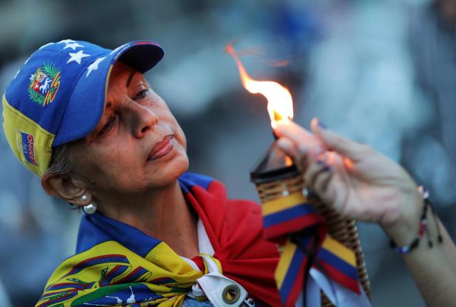 Une femme allume une torche en hommage aux victimes mortes durant le soulèvement raté de l'opération Liberté, le 5 mai 2019 à Caracas.