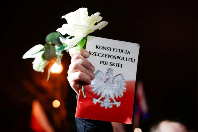 Un manifestant dispose d'une Constitution polonaise lors d'une manifestation à Cracovie, le 8 décembre 2017. Les législateurs polonais ont approuvé une refonte du système judiciaire, donnant au Parlement le contrôle de facto sur la sélection des juges défiant l'Union européenne.