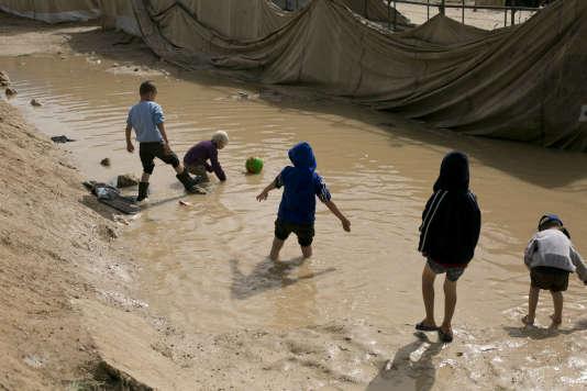 Des enfants jouent dans une flaque de boue, dans le camp d'Al-Hol, en Syrie, le 31 mars, où se propagent lecholéra et la tuberculose.