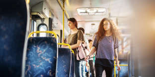A group of people is standing in a bus waiting to reach their destination with two young beautiful women infront.