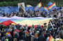 Participants in a protest hold copies of the posters and a giant rainbow flag in support of Elzbieta Podlesna, in Warsaw, Poland, Tuesday, May 7, 2019. Rights groups and government critics in Poland are protesting Tuesday after police temporarily detained Podlesna, a human rights activist, for putting up posters depicting the country's most revered Catholic icon with the LGBT rainbow on the halos of Mary and baby Jesus. (AP Photo/Czarek Sokolowski)