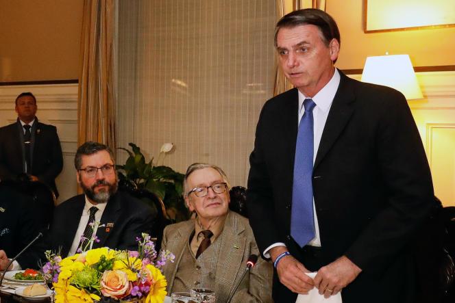 Le président brésilien Jair Bolsonaro (debout) à côté d'Olavo de Carvalho, référence de l'extrême droite, à Washington le 17 mars.