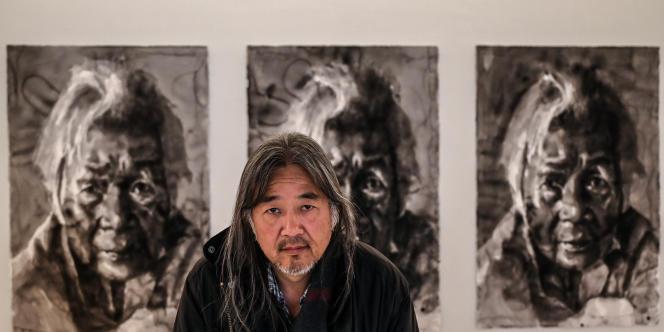 L'artiste franco-chinois Yan Pei-Ming pose pour une séance photo au Musée des beaux-arts de Dijon, le 18 avril 2019, devant les portraits de sa mère décédée récemment.