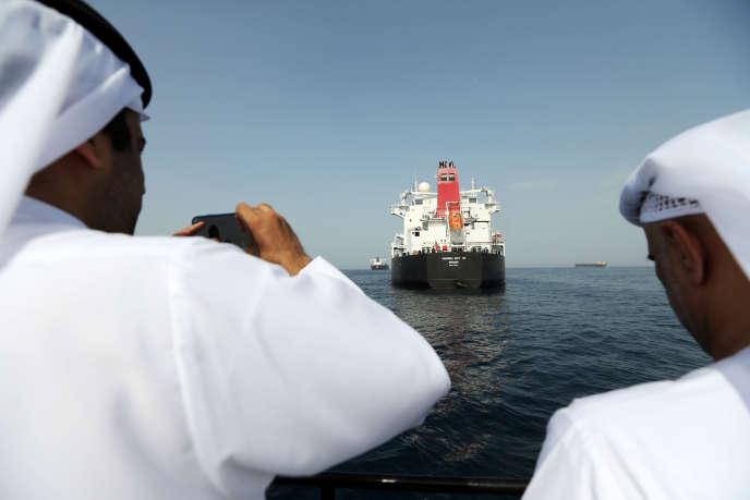 Des responsables du port de Foujeyra photographient, lundi 13 mai, le « Andrea Victory», l'un des quatre navires endommagés lors d'« un acte de sabotage» la veille.