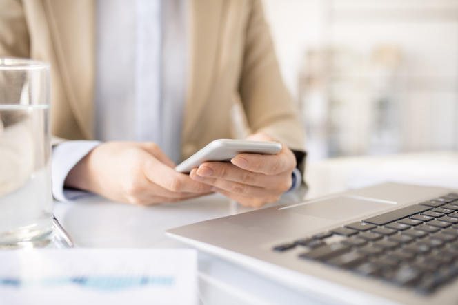 Close-up of unrecognizable businesswoman sitting at desk and using mobile phone while checking messages in messengers at workplace