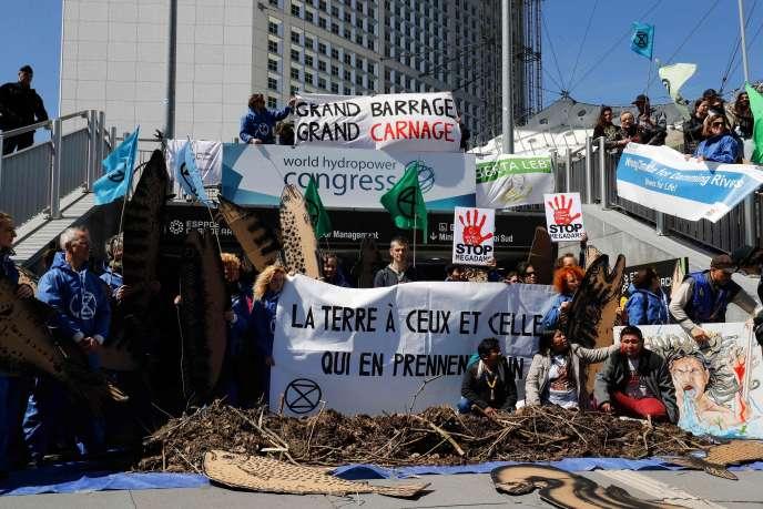 Des militants du mouvement Extinction Rebellion et de l'ONG Planète Amazone se sont mobilisés, mardi 14 mai à La Défense, contre les projets de grands barrages, à l'occasion de l'ouverture du Congrès mondial de l'hydroélectricité.