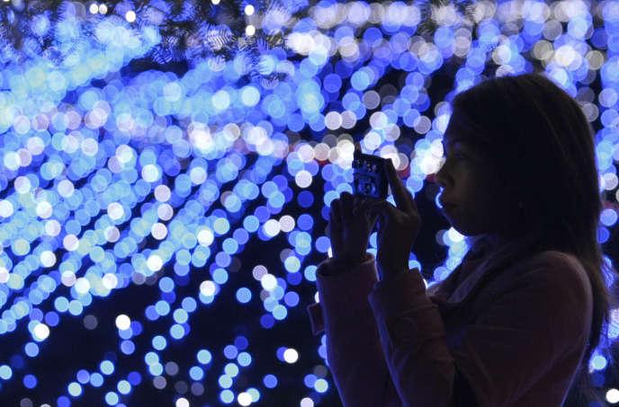Une femme prend en photo une installation de LED bleues à Tokyo en 2009.