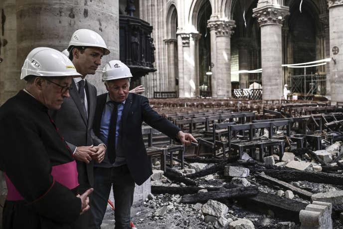 L'architecte en chef des monuments historiques (ACMH) Philippe Villeneuve (à droite) en compagnie du premier ministre canadien, Justin Trudeau (au centre), et le recteur archiprêtre de la cathédrale, Patrick Chauvet, lors d'une visite dans les décombres de Notre-Dame, à Paris, le 15 mai.