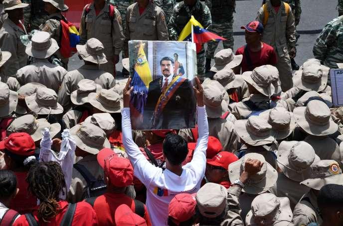 Un homme brandit un portrait de Nicolas Maduro, lors d'une manifestation à Caracas, le 1er mai.