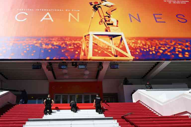 Staff members install the red carpet outside the festival palace on May 14, 2019 ahead of the opening of the 72nd edition of the Cannes Film Festival in Cannes, southern France. / AFP / Christophe SIMON