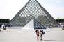 Des touristes stand devant la pyramide du Louvre à Paris, septembre 2016.