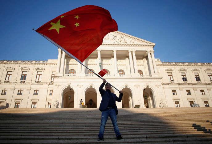 Un homme agite le drapeau chinois devant l'Assemblée de la République du Portugal, avant la rencontre entre le président chinois Xi Jinping et le président du Parlement, Eduardo Ferro Rodrigues, à Lisbonne le 5 décembre 2018.