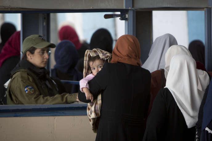 Des Palestiniens passent entre Ramallah et Jérusalem àKalandia, le 10 mai.