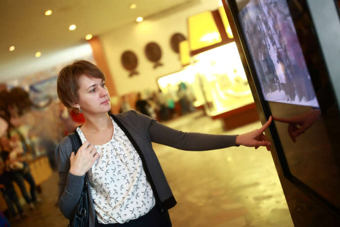 Woman using touch screen in a museum
