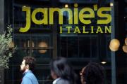 Des passants devant un restaurant fermé de l'enseigne Jamie's Italian, mardi 21 mai, à Londres.