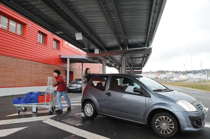 Une clienterécupère ses courses sur le parking du drive d'un supermarché Auchan, à Mantes-la-Jolie, en février 2010.