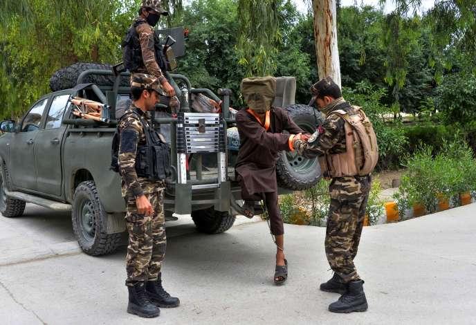 Les forces de sécurité afghanes escortent des combattants présumés des talibans et de l'organisation Etat islamique, à Jalalabad, à l'est de Kaboul, le 23 mai.
