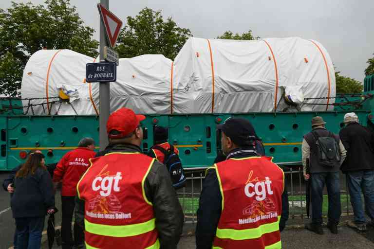 General Electric's employees and union representatives demonstrate to keep their plant in operation in front next to a convoy carrying the 9HA.02 GE turbine on May 21, 2019, in Belfort, eastern France. US energy giant General Electric plans to slash up to 468 jobs across France, union sources said January 22, 2019. 229 jobs would be cut from the staff at Alstom Power Systems (APS), including 146 at GE Energy's European headquarters in Belfort, eastern France. / AFP / SEBASTIEN BOZON