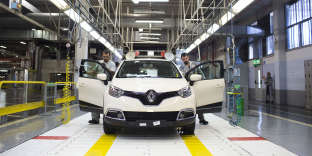 """Workers make quality control checks on a completed Renault Captur compact sport-utility vehicles (SUV) following assembly at the Renault SA automobile plant in Valladolid, Spain, on Friday, July 11, 2014. Sales of Dacia models and the Renault Captur vehicle enabled the French company """"to diminish the impact of the decline in our main emerging markets and to maintain the group's positive momentum,"""" Chief Performance Officer Jerome Stoll said in the statement. Photographer: Angel Navarrete/Bloomberg via Getty Images"""