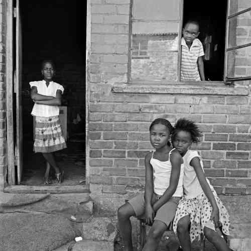«Pendant dix ans, de 2004 à 2014, l'Américaine Anne Rearick a photographié les habitants d'un township situé près du Cap en Afrique du Sud. Ses photos en format carré noir et blanc dépeignent un quotidien qui a peu changé depuis l'apartheid : même si la vie et l'habitat est précaire, les gens sont dignes comme ces enfants qui posent fièrement devant leur maison ».