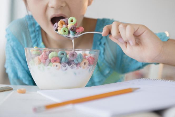Une fillette mange un bol de céréales ultratransformées.