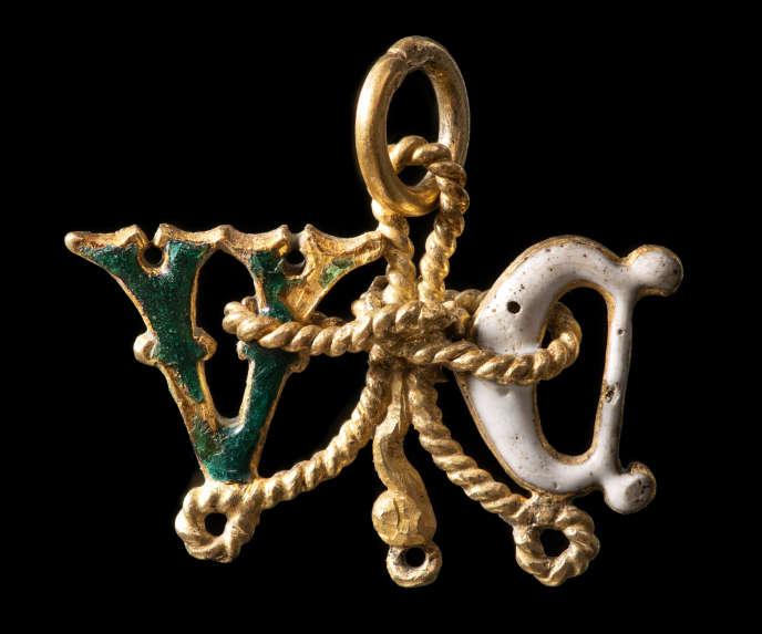 Ce médaillon reproduit deux initiales, sans doute un D et un V. Chacune montre une face recouverte d'émail vert translucide et une face recouverte d'émail blanc. Ces lettres sont unies par des motifs de cordelettes qui donnent l'impression d'un nœud médian.