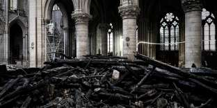 A worker stands on scaffolding near to damages and rubble during preliminary work in the Notre Dame de Paris Cathedral one month after it sustained major fire damage on May 15, 2019, in Paris. - The April 15, fire destroyed the roof and steeple of the 850-year-old Gothic cathedral. Images of the ancient cathedral going up in flames sparked shock and dismay across the globe as well as in France, where it is considered one of the nation's most beloved landmarks. (Photo by Philippe LOPEZ / various sources / AFP)
