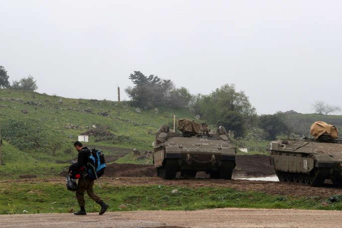 Un soldat passe devant des véhicules blindés de l'armée israélienne sur le plateau du Golan occupé par Israël, le 25 mars.