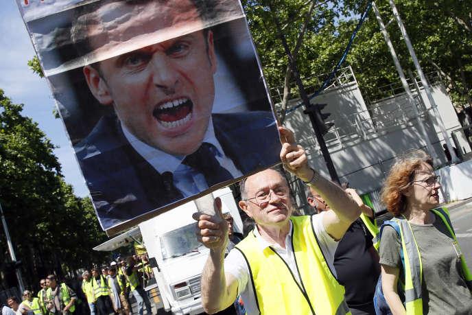 Un« gilet jaune» brandit un portrait d'Emmanuel Macron, lors d'une manifestation le 1er juin, à Paris.