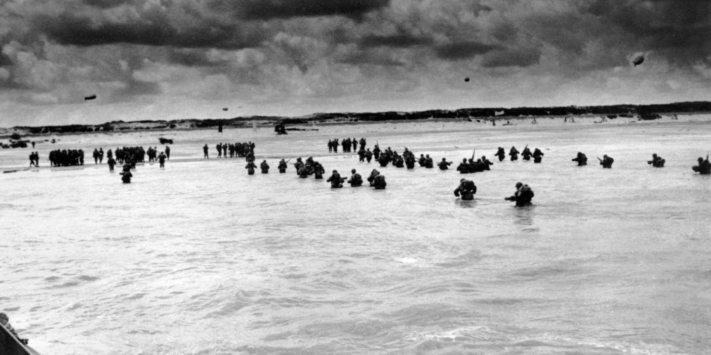 FILE - In this June 1944, file photo, U.S. reinforcements wade through the surf as they land at Normandy in the days following the Allies', D-Day invasion of occupied France. June 6, 2019, marks the 75th anniversary of D-Day, the assault that began the liberation of France and Europe from German occupation, leading to the end World War II. (U.S. Coast Guard via AP, File)