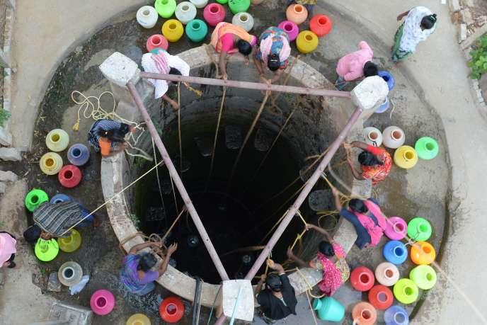 Des habitants boivent l'eau d'un puit, le 29 mai, près deChennai, l'ancienne Madras.