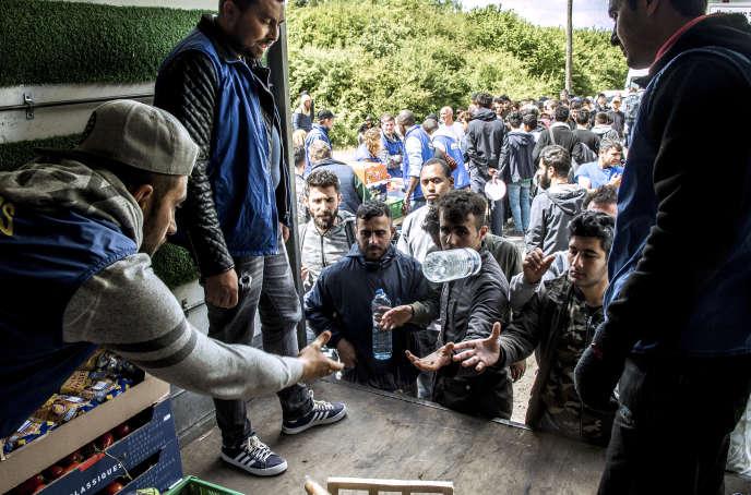 Des migrants attendent de recevoir de l'eau et de la nourriture fournies par l'association Emmaüs, le 12 mai 2017 à Grande-Synthe.