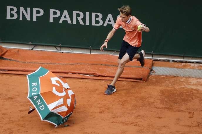 Porté par une rafale, le parapluie d'un spectateur a atterri sur le court.