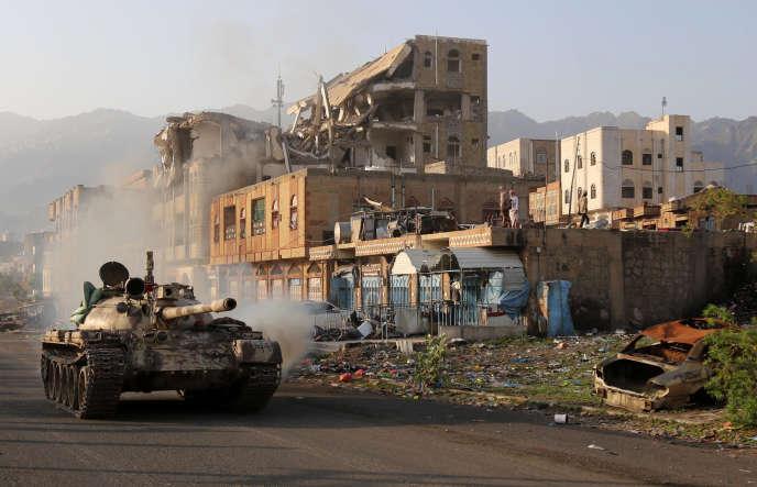 Des combattants yéménites, fidèles au président exilé Abd Rabbo Mansour Hadi, circulent à côté d'un bâtiment détruit lors d'un affrontement avec des rebelles chiites, dans la troisième ville du pays, Taez, le 30 mai 2019.